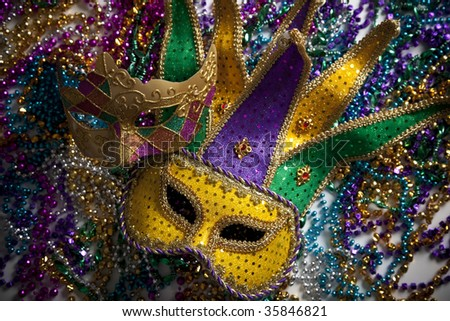 A group of mardi gras beads and mask with copy space - stock photo