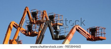 A Group of Mechanical Cherry Picker Lifts. - stock photo