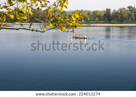 A group of men and women in the boat, rowing in the calm lake - stock photo