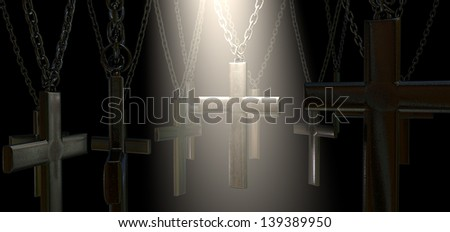 A group of metal crucifixes hanging from chains and a spiritual spotlight highlighting one in particular on a dark background