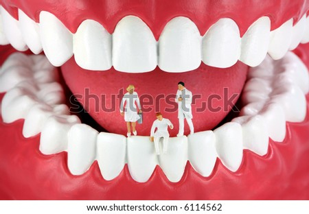 A group of miniature dentists and a dental assistant standing/sitting on human teeth. - stock photo