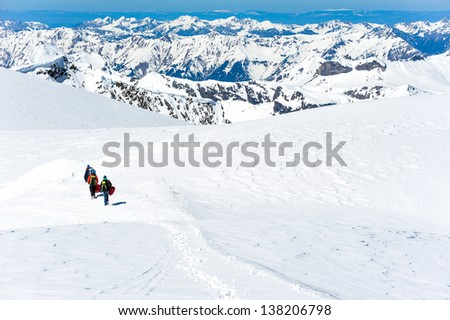 A group of mountain hiker walking on the snow into the mountain - stock photo