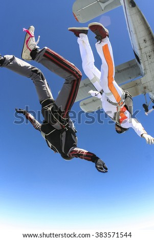 A group of paratroopers jumping out of an airplane. - stock photo