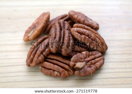 a group of pecan halves on wooden flat - stock photo