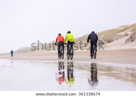 a group of people are biking on a beach