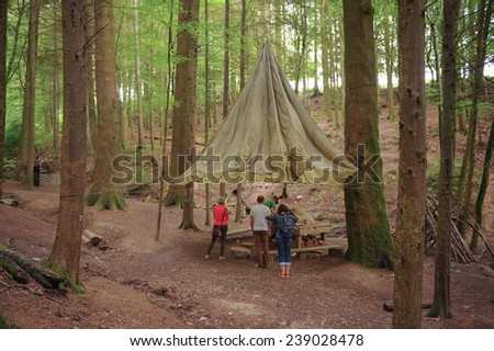 A Group of People Around A Makeshift Tent in A Woodland Clearing In the Woods Around Arlington, near Barnstaple, in the County of Devon, England, UK - stock photo
