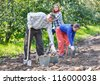 A group of people digging up potatoes. Harvested - stock photo