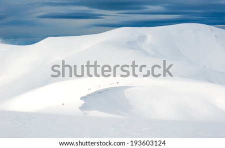 A group of people go on a winter snow-covered mountains