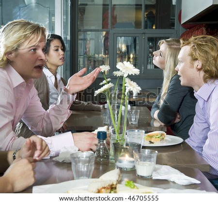 A group of people having lunch in a restaurant - stock photo