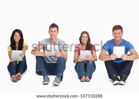 A group of people holding their tablet pc's in their hands as they all look at the camera - stock photo