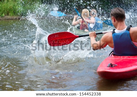 A group of people kayaking down a river - stock photo