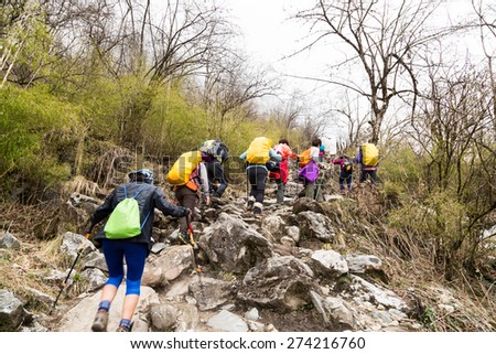 A group of people trekking an ascending rocky trail to the mountains - stock photo