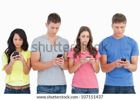 A group of people using their phones and sending texts as they stand beside each other