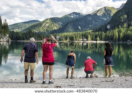 a group of people watching a lake in front of mountains