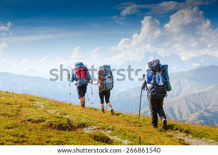 A group of people with backpacks walking on the trail - stock photo
