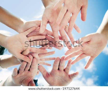 A group of people with their hands all in the middle.