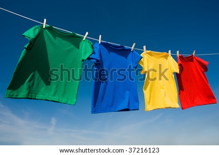 A group of primary colored t-shirts on a clothesline in front of blue sky