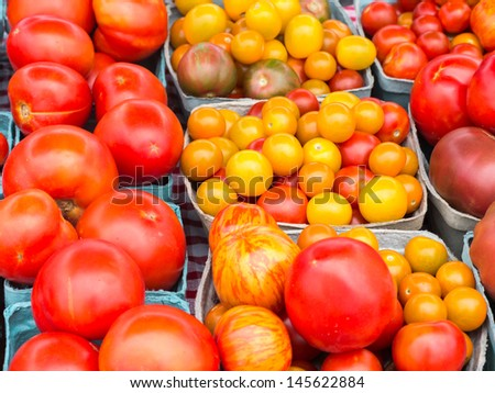 A group of red and yellow tomatoes of varying size at Delaware farm market.