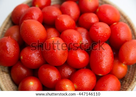A group of red, juicy and fresh plum tomatoes on a basket