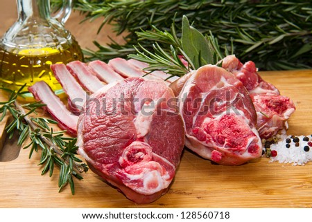 a group of rib lamb with oil and rosemary on wood table - stock photo