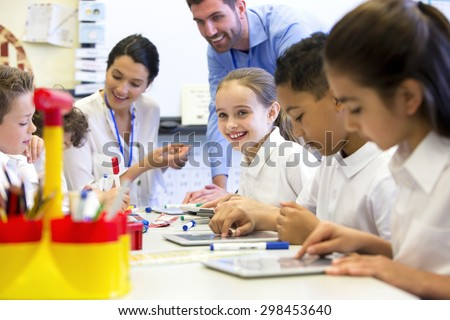 A group of school children can be seen working on digital tablets, two teachers can be seen behind them helping and supervising - stock photo