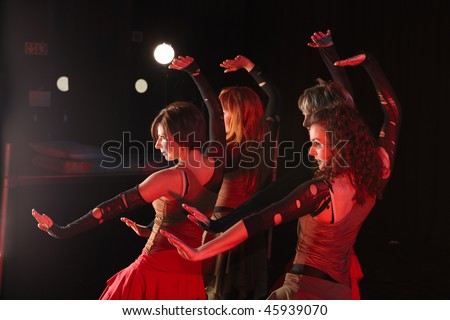A group of sexy young freestyle dancers on a dark stage with red and blue stage lights