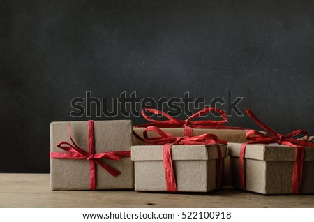 A group of simple, rustic gift boxes, with closed lids and red raffia ribbon bows, on oak table with black chalkboard background providing copy space.