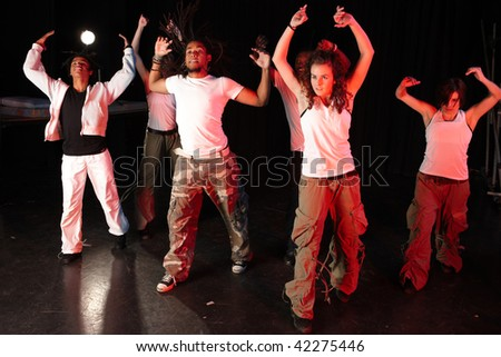 A group of six female and male freestyle hip-hop dancers during dance training session on stage. Lit with spotlights - stock photo