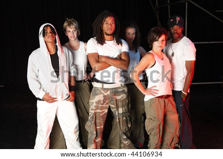 A group of six female and male freestyle hip-hop dancers. Lit with spotlights