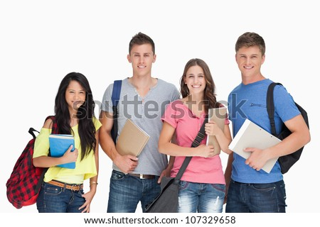 A group of smiling students as they look at the camera while holding notepads and backpacks