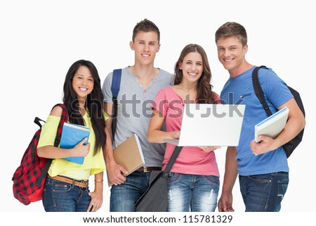 A group of smiling students looking at the camera while one holds a laptop