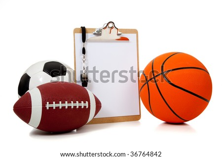 A group of sports ball with a blank clipboard including a basketball an American football and a soccer ball on white - stock photo