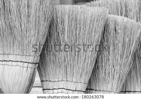 a group of straw brooms - stock photo