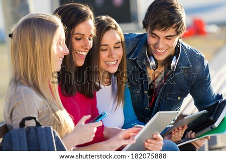 A group of students having fun with smartphones and tablets after class