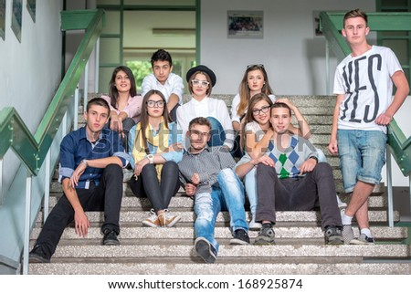 A group of students sitting on school stairs posing - stock photo