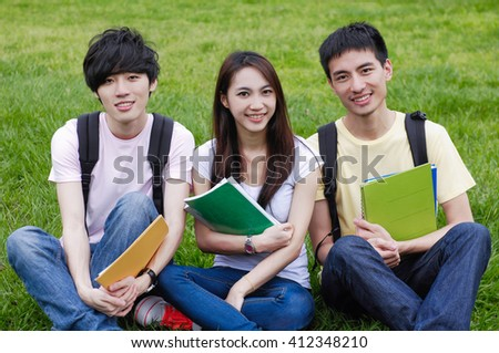 A group of students sitting together with books at a campus - stock photo