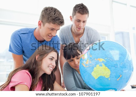 A group of students smile while searching the globe for a country