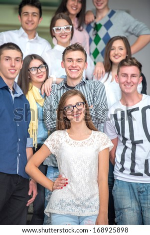 A group of students standing on school stairs smiling - stock photo