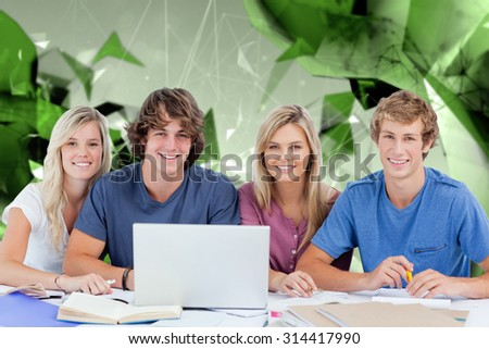 A group of students with a laptop look into the camera against angular design - stock photo