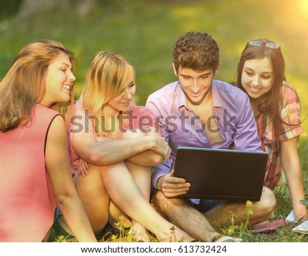 a group of students with laptop relaxing in the Park on Sunny day