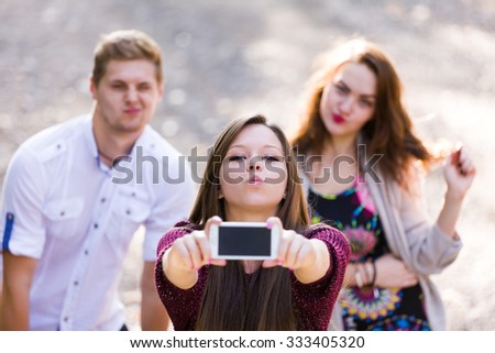 A group of teenagers playing around, taking a selfie. - stock photo
