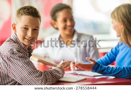 A group of teenagers sitting at the table in cafe and doing homework. - stock photo