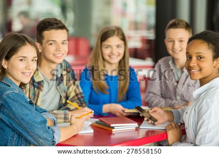 A group of teenagers sitting at the table in cafe and doing homework and looking at the camera. - stock photo