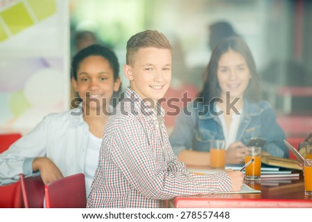 A group of teenagers sitting at the table in cafe, studying and drinking orange juice. Image through a glass. - stock photo