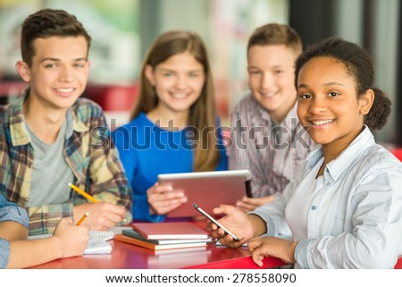 A group of teenagers sitting at the table in cafe, studying and using tablet. - stock photo
