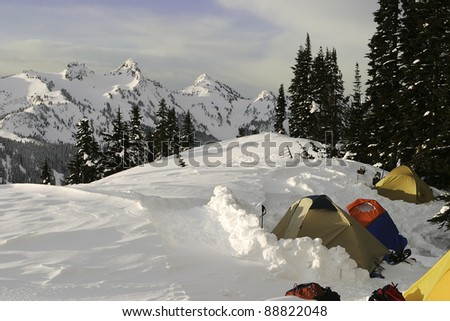 A group of tents high up on the side of Mt. Rainier in Washington State (US) is outlined against mountains of the Cascade range. This campsite was for an expedition of Boy Scouts. - stock photo
