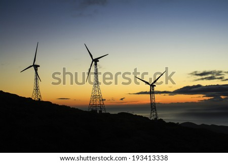 A group of three wind turbines at sunset in an eolic park - stock photo