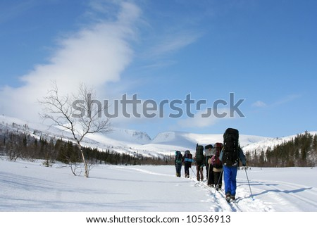 a group of tourists is in winter in low mountains