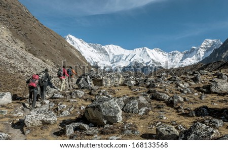 A group of tourists is on the moraine on the background of the massif Cho Oyu - Gokyo region, Nepal - stock photo