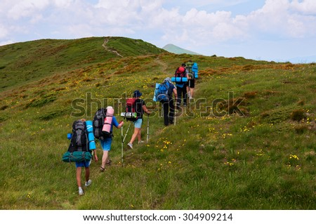 A group of tourists with large backpacks are on the sandy road to the mountain